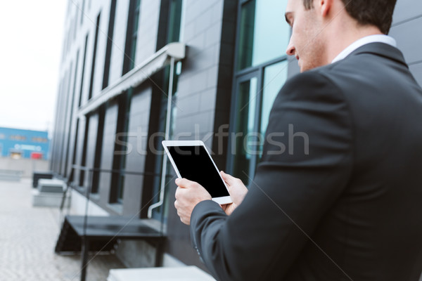 Back view of Business man with laptop near the office Stock photo © deandrobot
