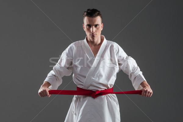 Young sportsman dressed in kimono tightening red belt Stock photo © deandrobot