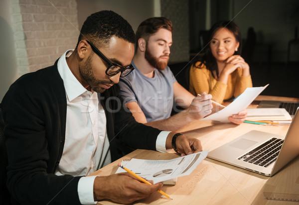 коллеги рабочих поздно ночь ноутбука документы Сток-фото © deandrobot