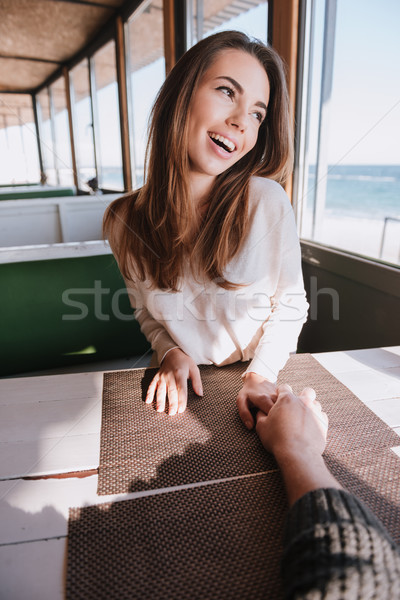 Vertical image laughing woman on date in cafe near sea Stock photo © deandrobot