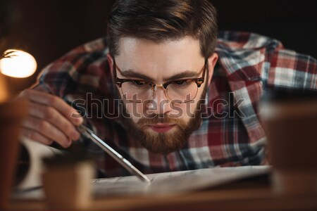 Concentrated young man holding lens while fixing vintage camera Stock photo © deandrobot