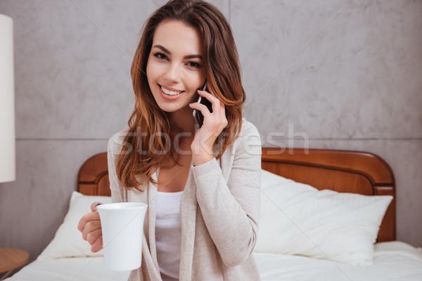 Mulher falante telefone móvel potável copo chá Foto stock © deandrobot