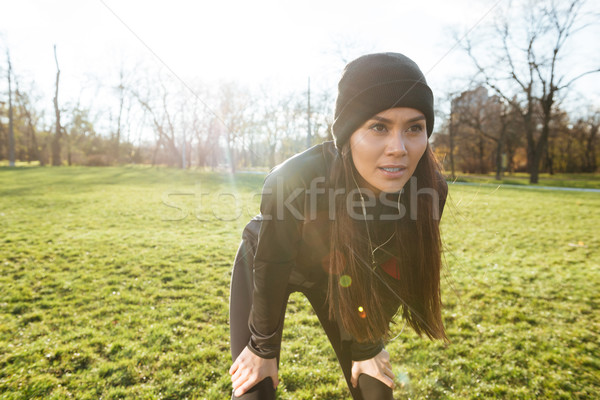 Female runner in warm clothes and earphones in autumn park Stock photo © deandrobot