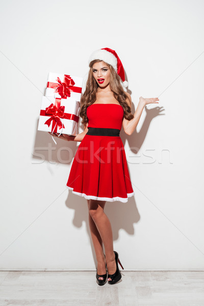 Vonzó barna hajú nő áll halom ajándékdobozok Stock fotó © deandrobot
