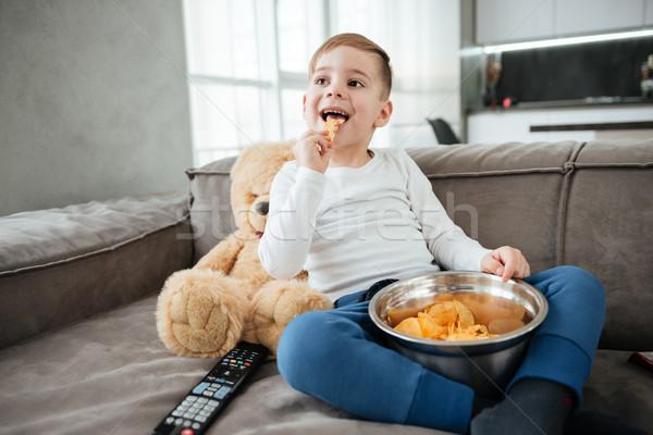 Erkek kanepe oyuncak ayı izlerken tv Stok fotoğraf © deandrobot