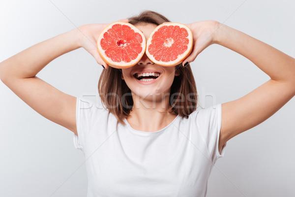 Derűs fiatal hölgy tart grapefruit kép Stock fotó © deandrobot