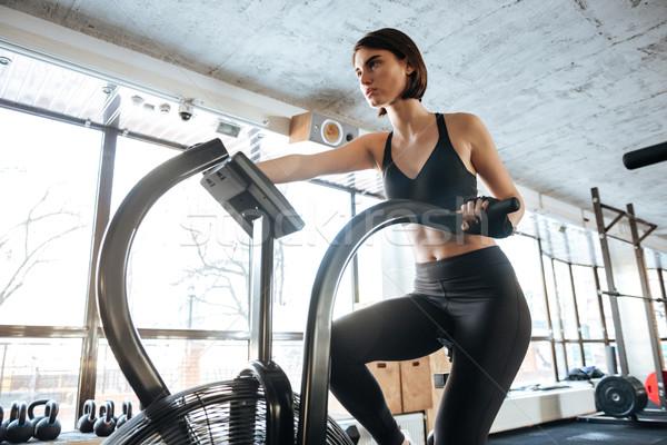 Sportswoman exercising on bike in gym Stock photo © deandrobot