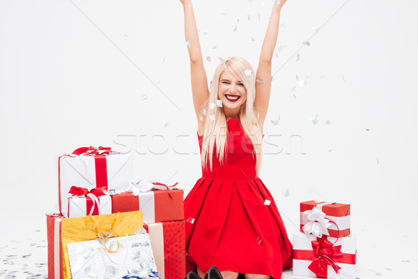 Woman in red dress having fun with heap of presents Stock photo © deandrobot