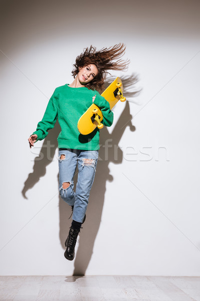 Skater beautiful young woman jumping. Stock photo © deandrobot