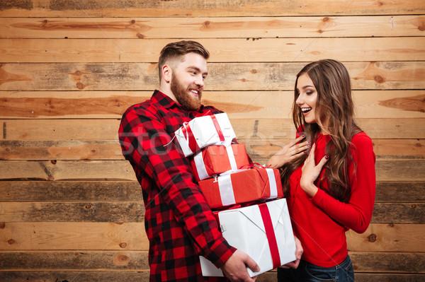 Happy joyful couple celebrating new year with heap of presents Stock photo © deandrobot