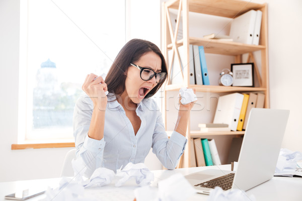 Angry businesswoman screaming while tear paper Stock photo © deandrobot