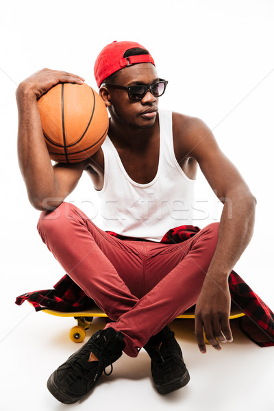 Handsome african man sitting on skateboard and holding basketball ball Stock photo © deandrobot