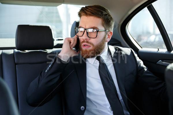 Frustrado homem de negócios óculos falante telefone móvel retrato Foto stock © deandrobot