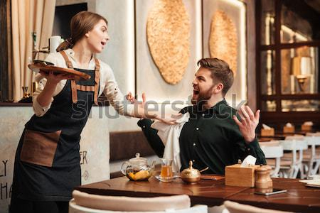 Happy bearded young man sitting in cafe Stock photo © deandrobot