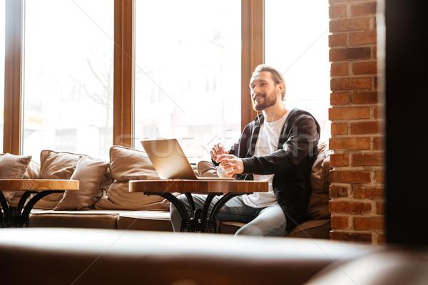 Barbuto uomo cafe laptop seduta tavola Foto d'archivio © deandrobot
