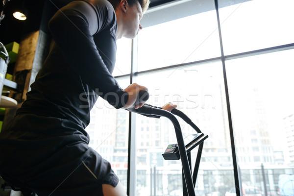Vista lateral muscular homem bicicleta ginásio janela Foto stock © deandrobot
