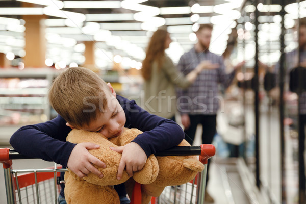 Happy boy in shopping trolley playing with teddy bear Stock photo © deandrobot