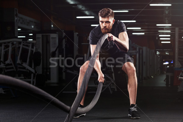 Concentrated handsome sports man make sport exercises Stock photo © deandrobot