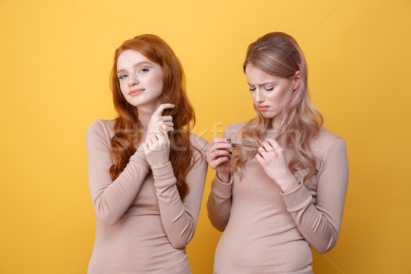 Cheerful redhead lady touching her hair near sad blonde woman Stock photo © deandrobot