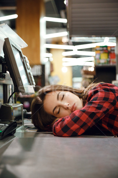 Cashier lady sleeping on workspace in supermarket shop. Stock photo © deandrobot