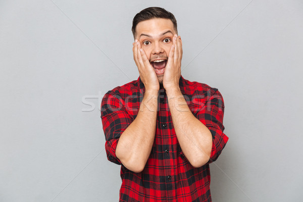 Surprised happy man holding his cheeks Stock photo © deandrobot