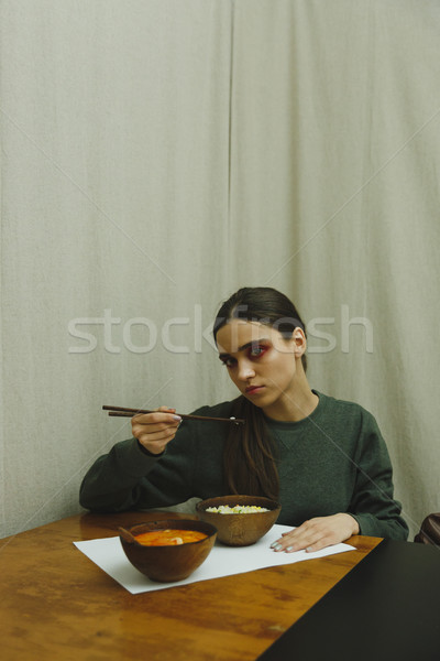 Vertical picture of young woman eating Stock photo © deandrobot