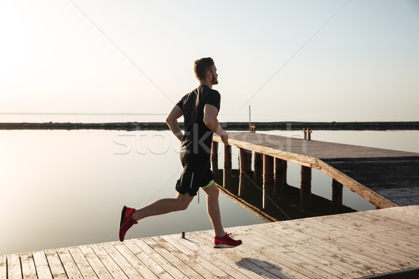 Back view full length portrait of a healthy sportsman running Stock photo © deandrobot