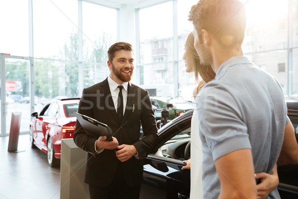 Smiling salesman showing new car to a couple Stock photo © deandrobot