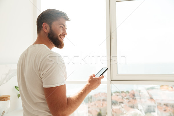 Back view of bearded man using his smartphone Stock photo © deandrobot