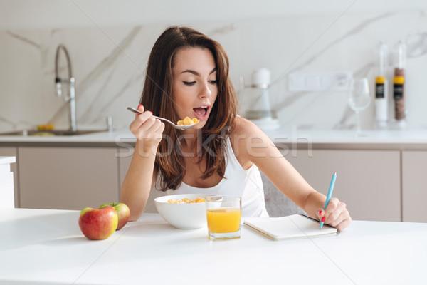 Dość młoda kobieta jedzenie zbóż śniadanie Zdjęcia stock © deandrobot