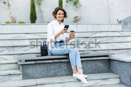 Young pretty woman sitting on stairs with laptop computer Stock photo © deandrobot