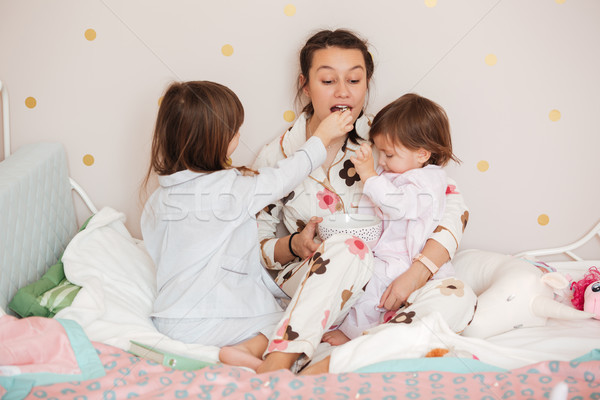 Daughters feed her mother Stock photo © deandrobot