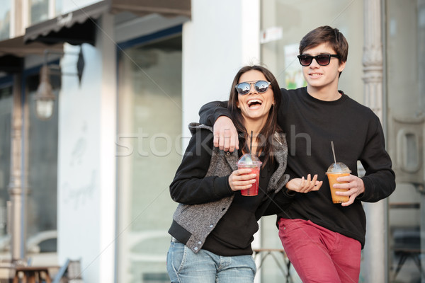 Smiling young lady walking outdoors with her brother Stock photo © deandrobot