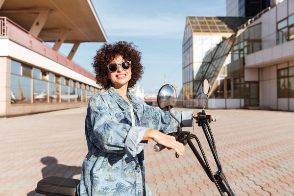 Vista laterale sorridere ragazza occhiali da sole posa moto Foto d'archivio © deandrobot