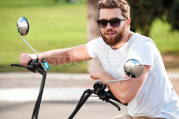 Alegre barbudo homem óculos de sol sessão moderno Foto stock © deandrobot