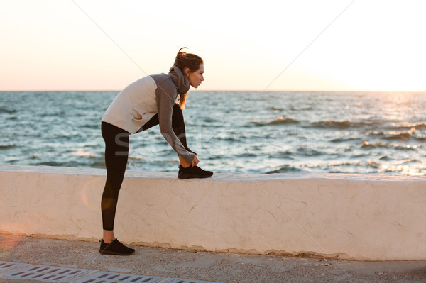 Portrait of young slim sport woman tying shoelace at the morning Stock photo © deandrobot