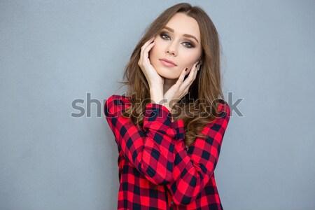 Fiatal nő piros kötött pulóver tart nyak Stock fotó © deandrobot