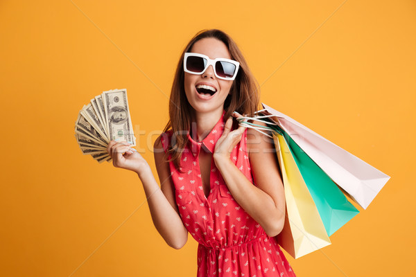 Photo of happy young woman in sunglasses holding fan of money an Stock photo © deandrobot