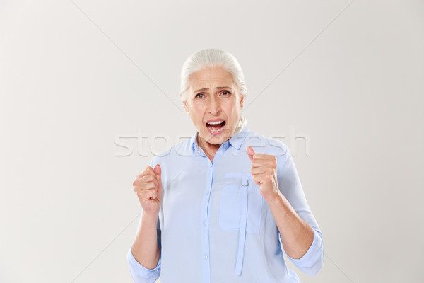 Photo of joyful elderly woman supporting something, looking at c Stock photo © deandrobot