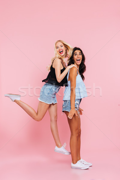 Full length image of two happy friends playing and rejoice Stock photo © deandrobot