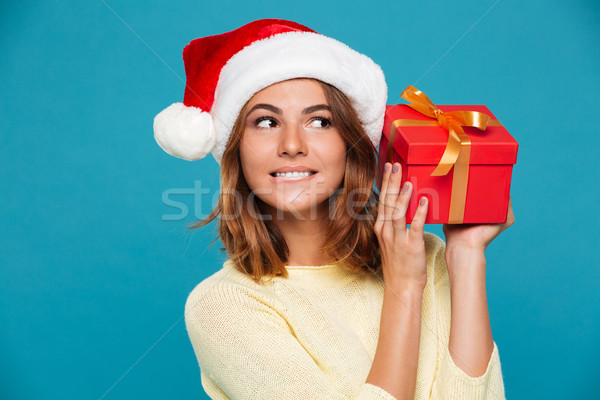 Pleased intrigued woman in sweater and christmas hat holding gift Stock photo © deandrobot
