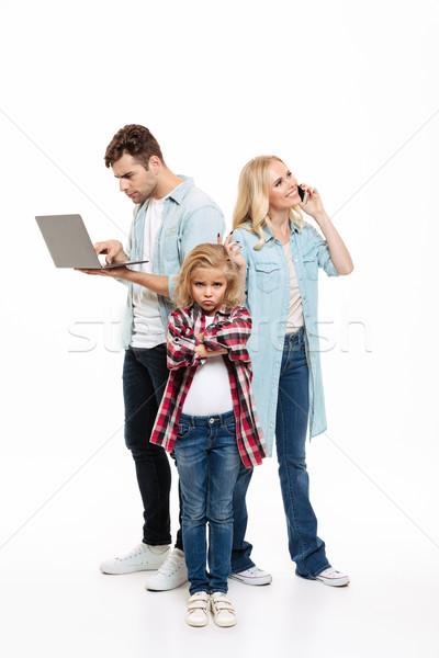 Full length portrait of a family talking on mobile phone Stock photo © deandrobot