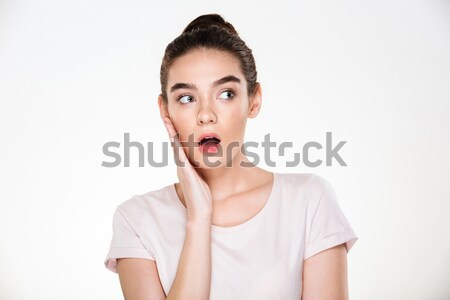 Pretty woman with brown hair in bun touching her face expressing Stock photo © deandrobot