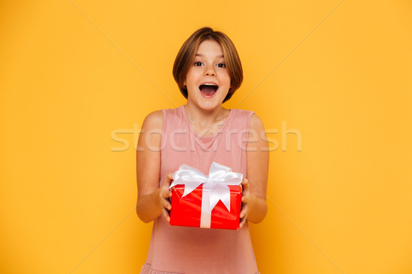 Happy surprised girl holding red present isolated over yellow Stock photo © deandrobot