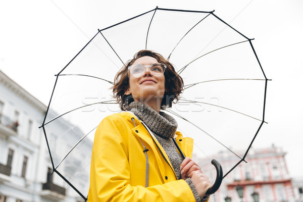 View from beneath of positive woman in yellow raincoat and glass Stock photo © deandrobot
