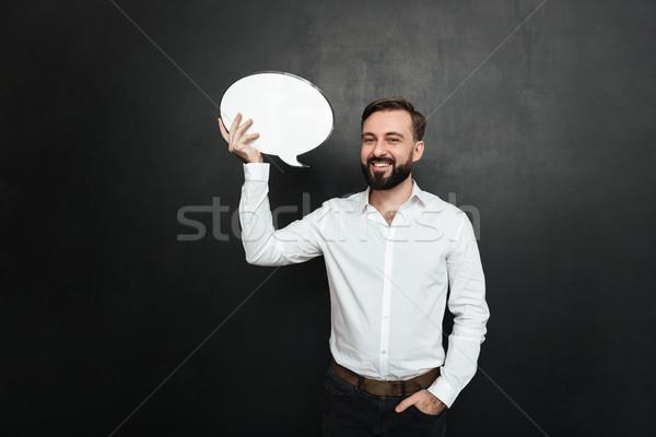 Stock photo: Good-looking brunette man holding blank speech bubble and lookin