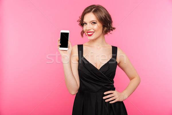 Portré mosolyog lány fekete ruha tart képernyő Stock fotó © deandrobot