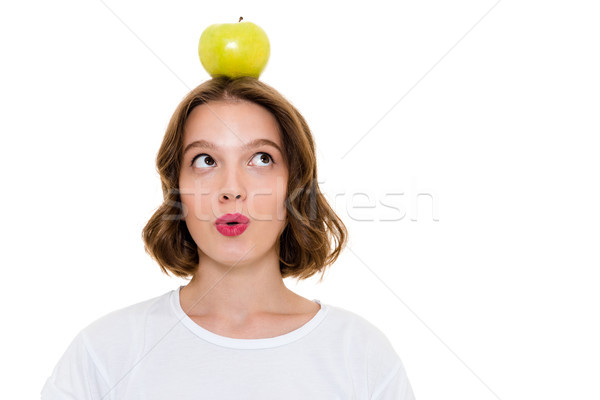 Thinking pretty caucasian woman holding apple on head Stock photo © deandrobot