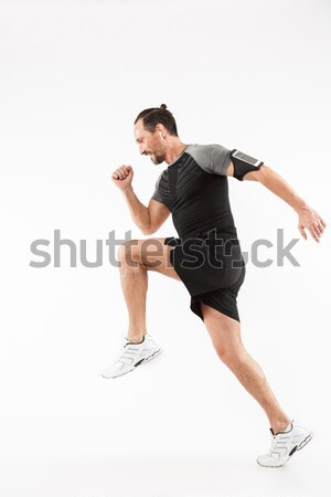 Full length image of Happy fitness woman moving in studio Stock photo © deandrobot