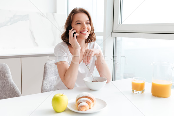 Happy charming woman in white tshirt speaking on mobile phone wh Stock photo © deandrobot